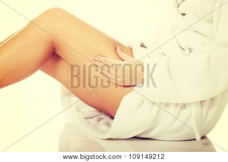 Spa woman checking cellulite on her thigh.