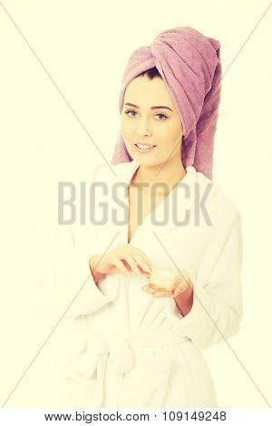 Spa woman in bathrobe and turban with cream moisturizer.