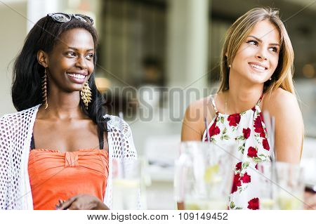 Young And Happy Friends Sitting Talking At A Table