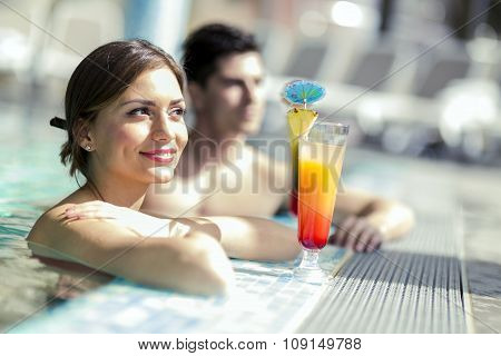 Young People Drinking Cocktails By The Swimming Pool And Relaxing