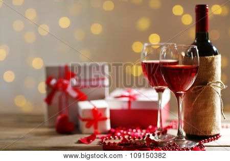 Setting of a bottle of wine, gifts in the boxes and other decoration, on blurred background