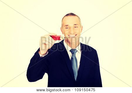 Businessman writing something with big red pencil.