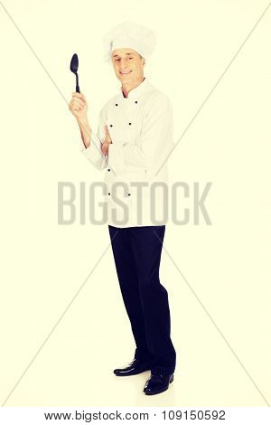 Restaurant chef holding black plastic spoon