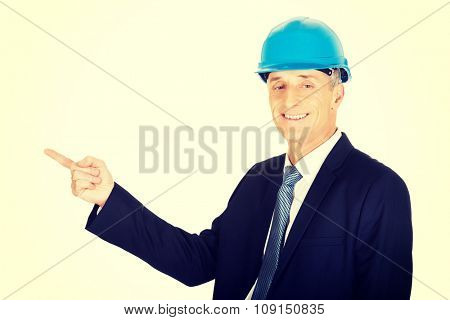 Constructor mature businessman pointing to the left.