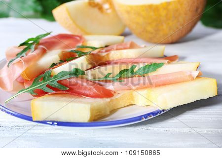 Melon with prosciutto of Parma ham on wooden table, closeup