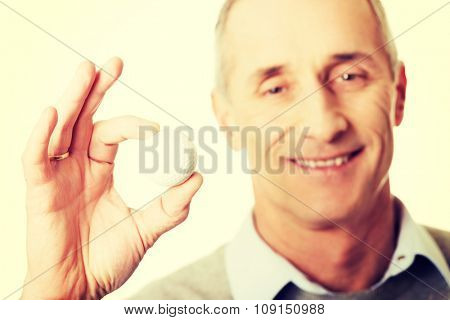 Smiling mature man holding golf ball.