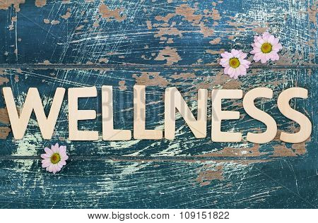 Wellness written on rustic wooden surface and pink daisy flowers