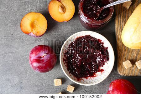 Tasty jam in the jar and on the plate, plums, crackers and fresh buns close-up