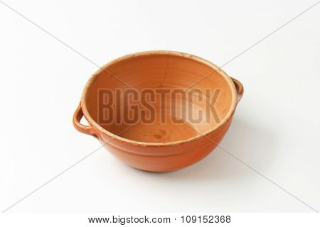 Empty round red clay bowl with two small handles