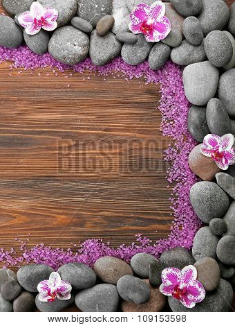 Spa stones and orchid on wooden background