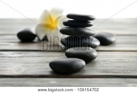 White plumeria flower with pebbles on wooden table