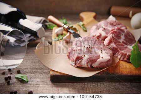Marbled beef steak and spices on wooden background
