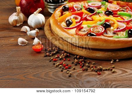Delicious pizza with vegetables, on wooden table