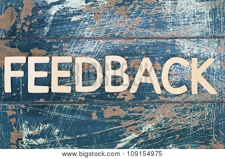 Word feedback written on rustic wooden surface