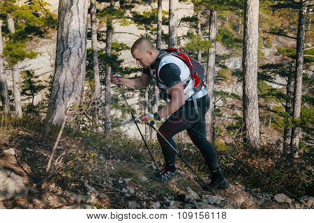 young male runner with walking poles climbs a mountain path up
