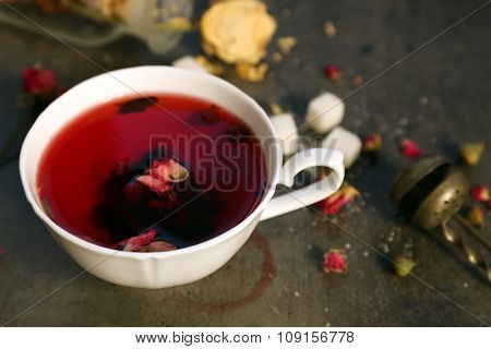 Cup of rose tea with sugar on wooden table