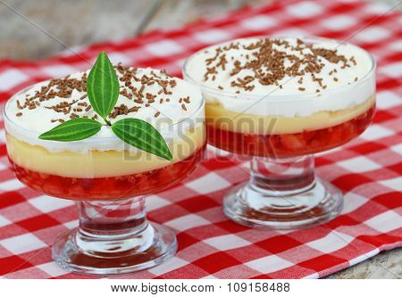 Trifle in dessert glasses on red and white checkered cloth on rustic wooden surface