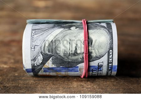 Dollars roll on wooden background
