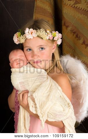 Pink little girl playing an angel in a Christmas nativity scene (the baby is a doll)