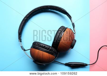 Black and brown headphones on pink-blue background