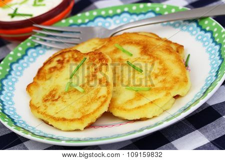 Golden potato fritters garnished with spring onions, closeup