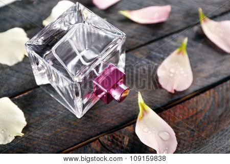 Bottle of perfume and rose petals on wooden background