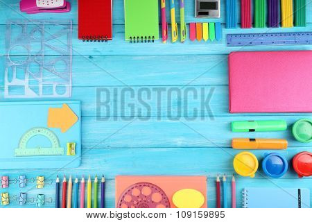 Frame of colourful stationary on blue wooden background