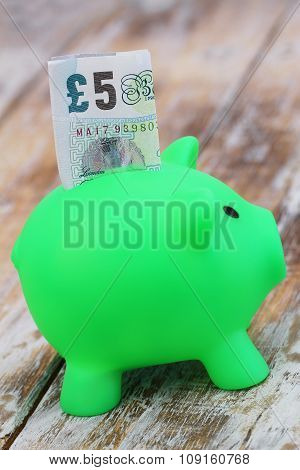 Five pound note sticking out of green piggy bank on rustic wooden surface