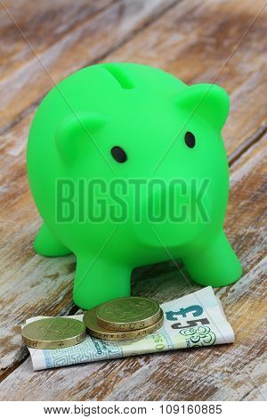 Five pound note and small change next to green piggy bank on rustic wooden surface