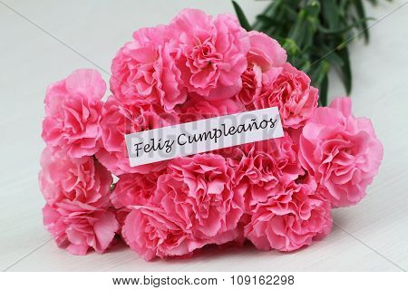 Feliz cumpleanos (Happy birthday in Spanish) card with pink carnations on rustic surface