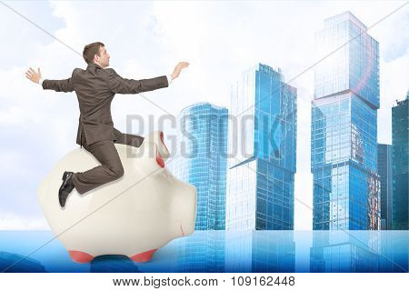 Man sitting on piggy bank and city