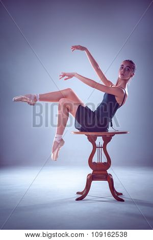 The silhouette of young ballerina on the wooden table
