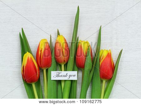 Thank you card with red and yellow tulips on white wood