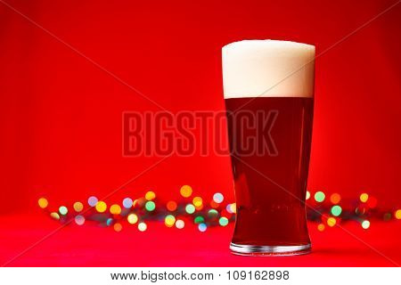 Full glass of bear or ale with blurred christmas lights in background