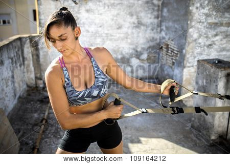 Woman Practicing Suspension Training On An Old Rooftop