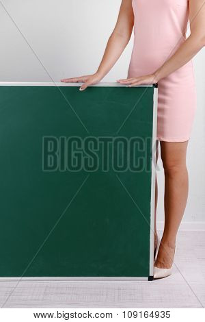 Woman in rosy dress with green blackboard, close up