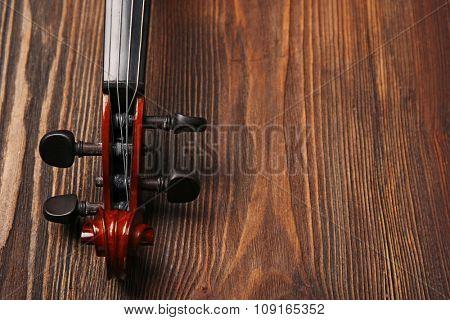Violin neck on wooden background