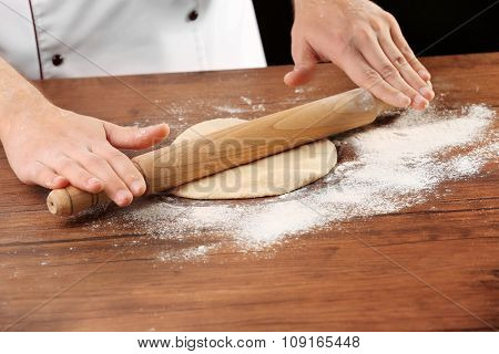 Hands rolling dough basis for pizza on the wooden table, close-up