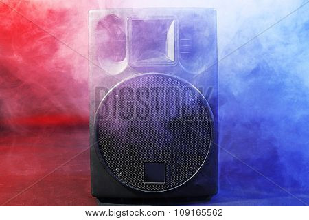 Black loudspeaker in dense smoke on dark background