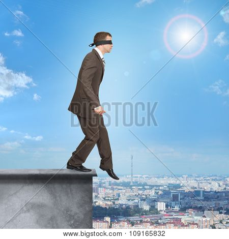Businessman walking from edge of building roof