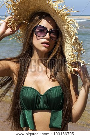 Portrait of woman in hat with sunglasses on beach. Beautiful smiling girl wearing green bikini poses