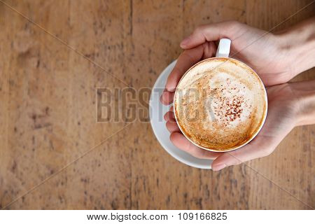 Cup of tasty cappuccino with hands on table