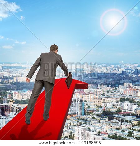 Businessman running on red arrow above city