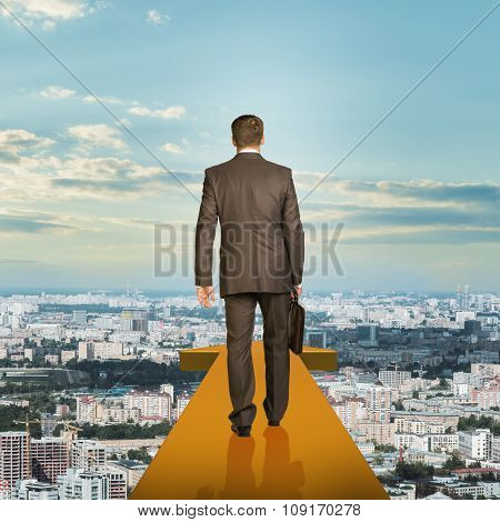 Businessman on gold arrow above city