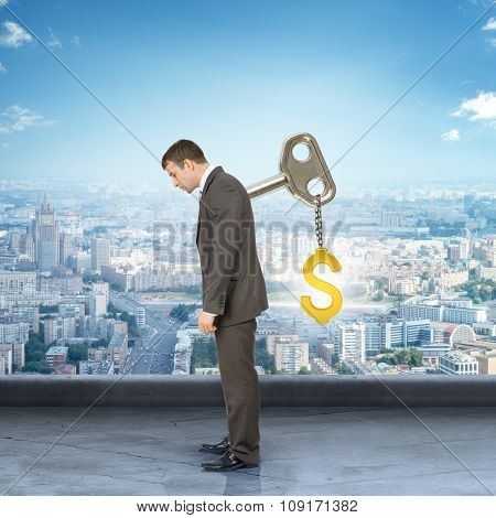 Businessman with key in back and dollar sign