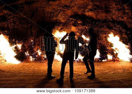 Men drinking in front of the burning rocks