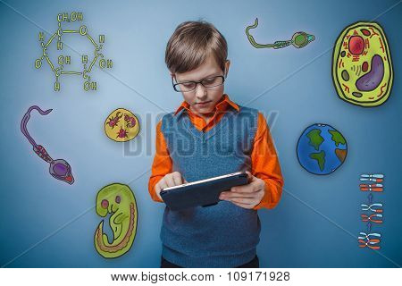 Teenage boy in glasses enthusiastically working on the tablet to