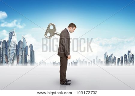 Businessman with key in back and city