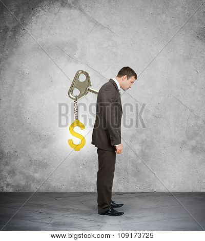 Businessman with key in back and gold dollar sign