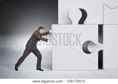 Businessman pushing puzzle piece